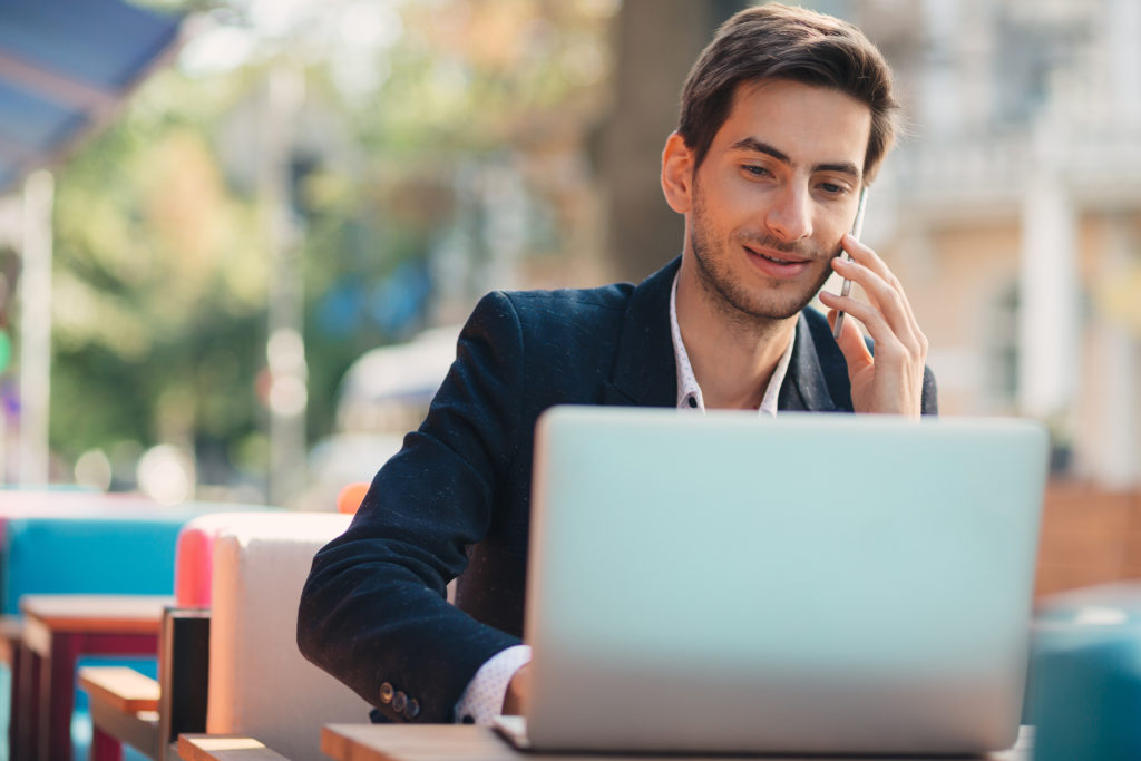Young entrepreneur working on laptop and phone